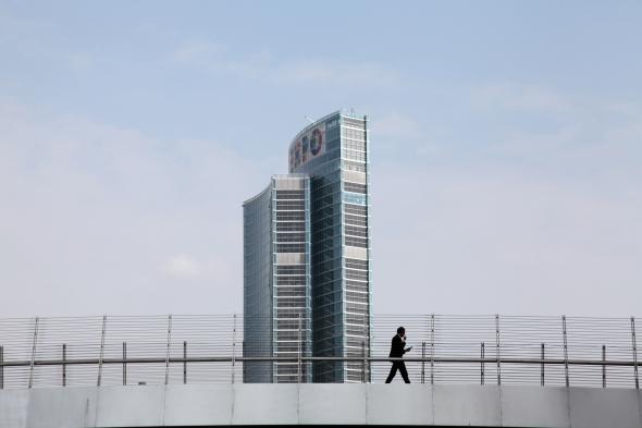 october 2014. A man walking on a bridge under the brand new Lombardy Region headquarter.