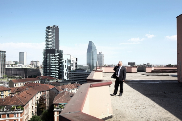 april 2014. A man phoning on the roof of an old building surrounded by the new city.